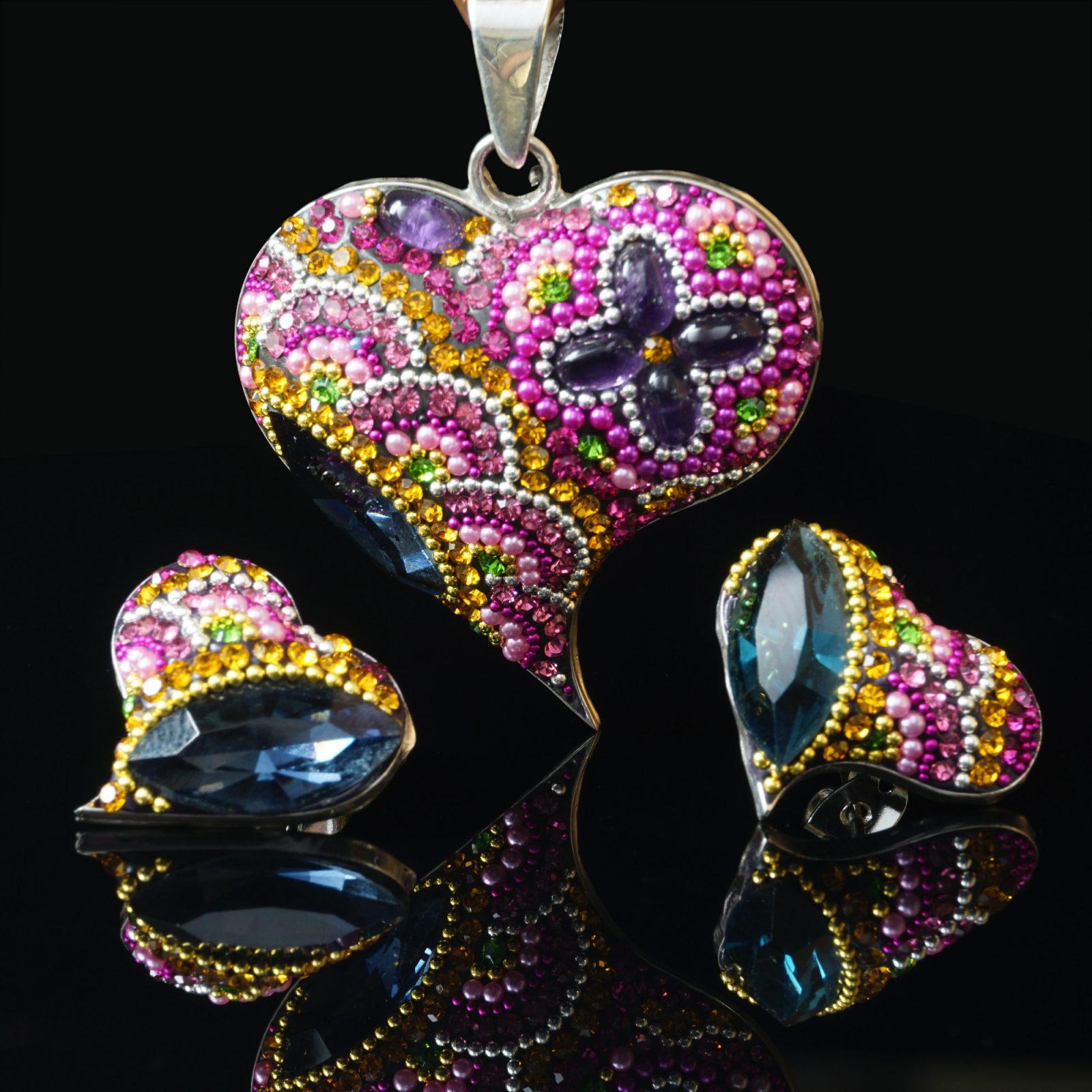 Fantastiskt hjärta: Hänge och örhängen med form av hjärta gjord av glansiga kristaller och sterling silver som ram.