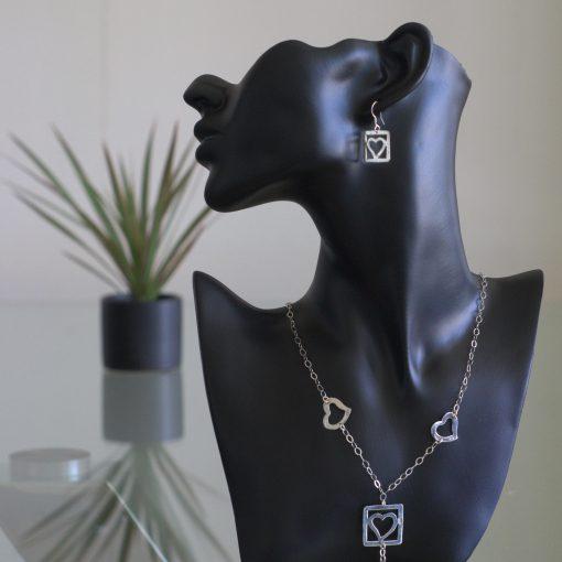 Ross: kombination av halsband, berlock och örhängen. Glansig sterling silver med ringar, rutor och hjärter
