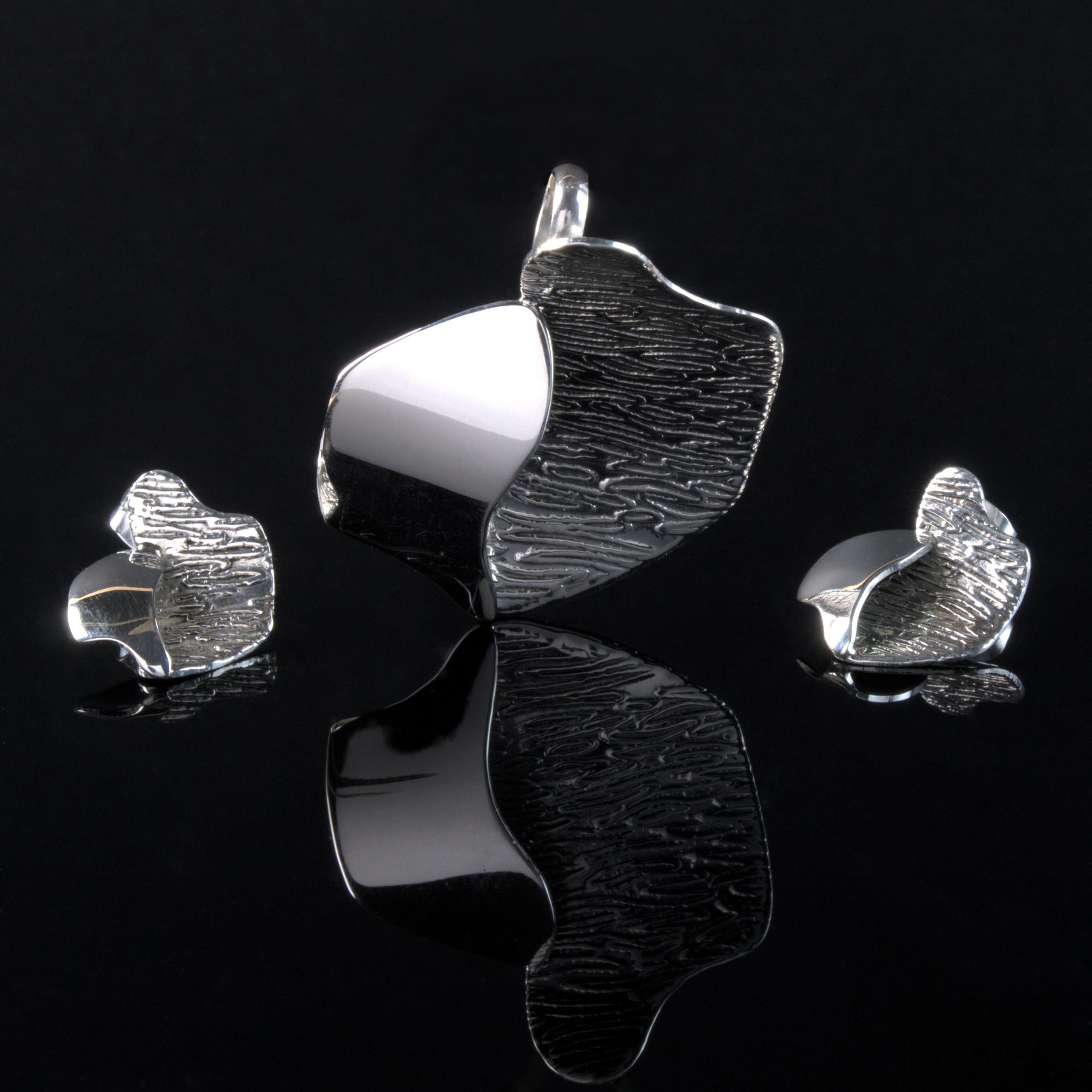 Atria: Örhängen och berlock med ojämt form. Randig finish och sterling silver material.