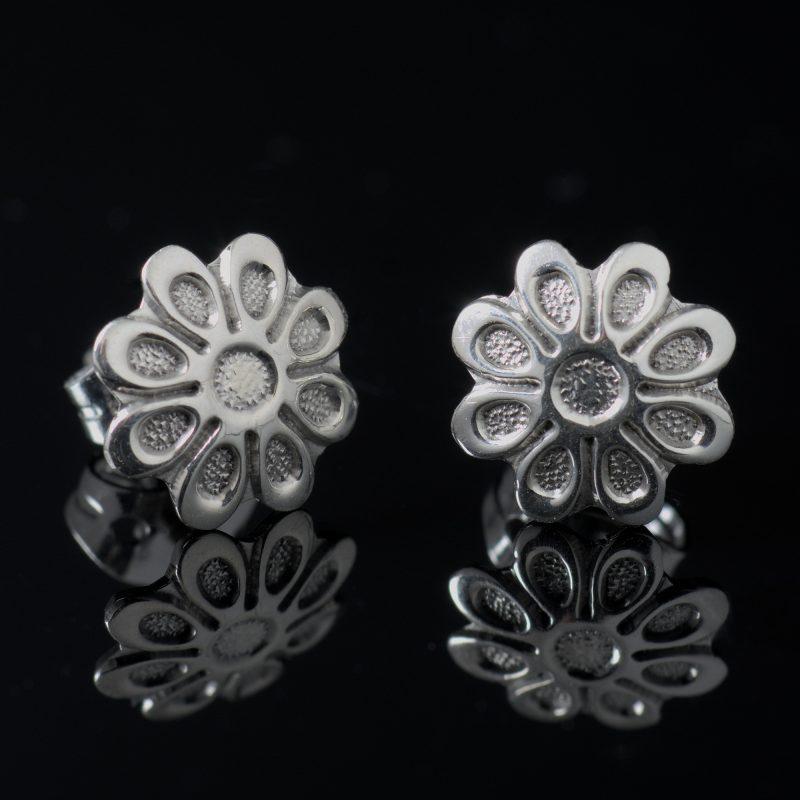 Glansiga och randiga örhängen med blomma form och sterlingsilver material.