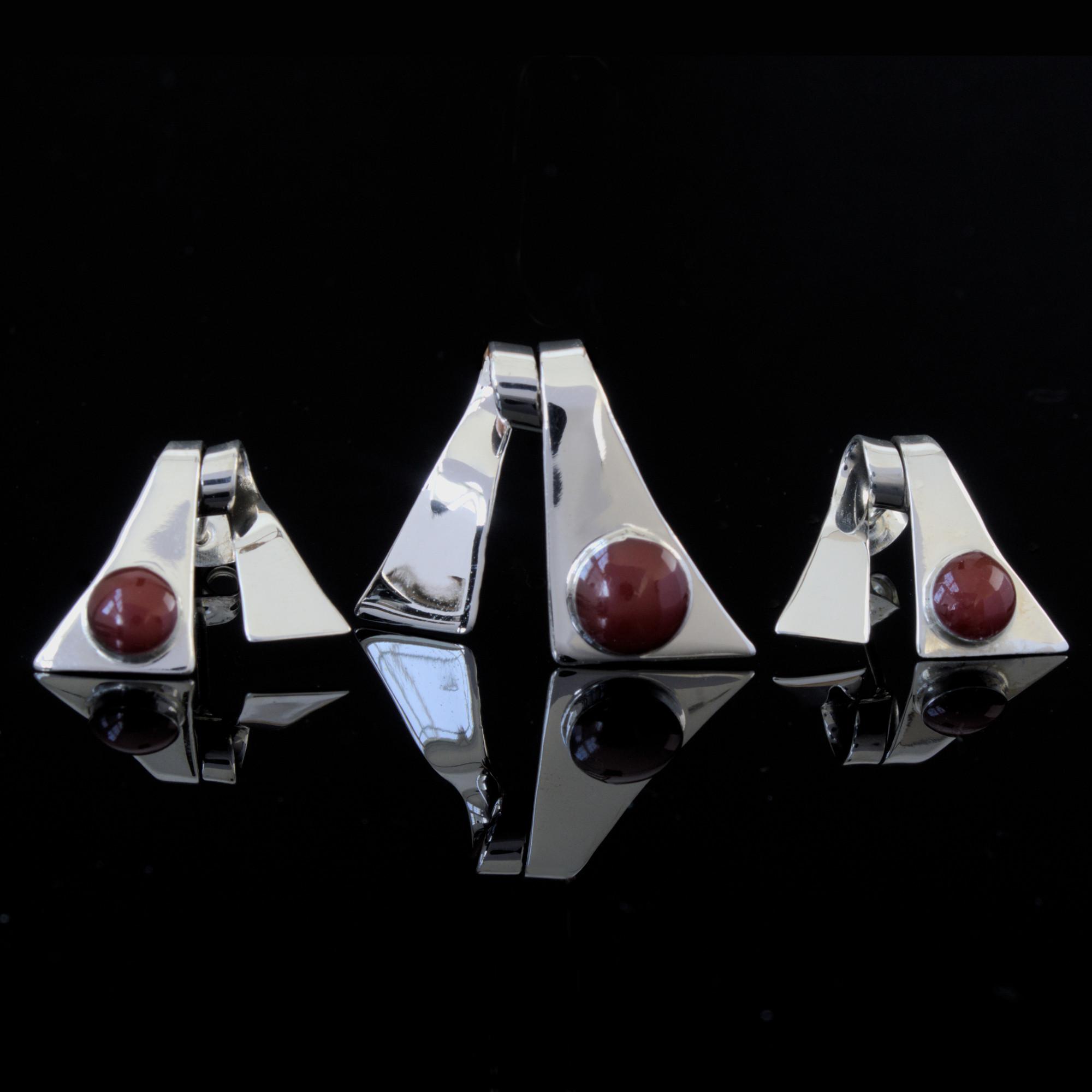 Orion: Örhänge och berlock med trialgel form. Material är sterling silver och kristaller. Glansiga.